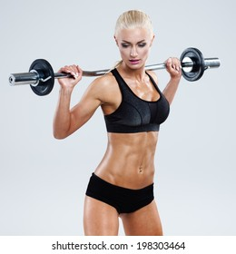 Athletic woman pumping up muscles with barbell on gray background