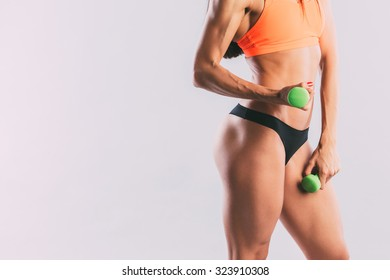 Athletic woman pumping up muscles with dumbbells close-up.