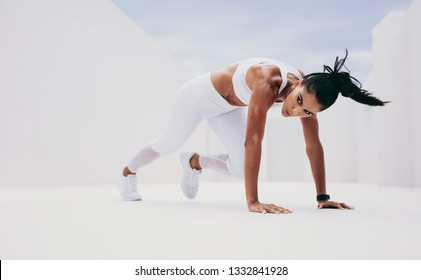 Athletic woman in push up position bringing her leg forward. Woman doing fitness training with her hands on the floor.