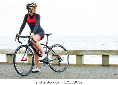 Athletic woman riding bicycle near sea. Beautiful sporty woman in helmet and sportswear cycling near body of water during daytime. Triathlon concept