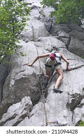 Athletic woman rock climbing on a high rock wall