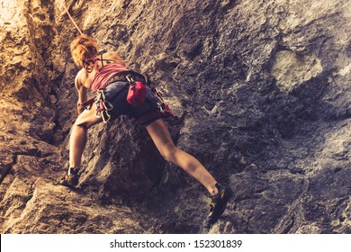 Athletic woman rock climbing at sunset