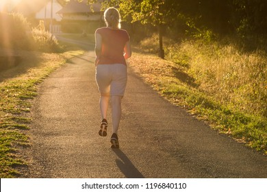 Athletic woman running at countryside trail in sunrise light. Beautiful female running outside in leafy and green suburb.