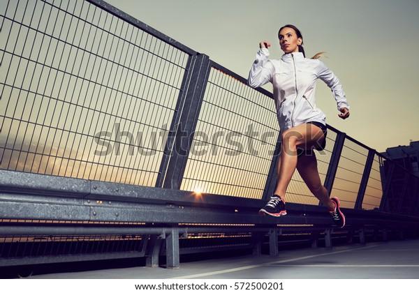 Athletische Frau, die bei Sonnenuntergang auf dem Dach des Parkplatzes, Garage
