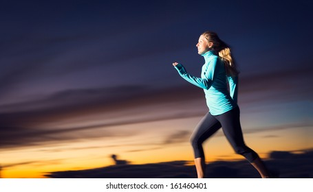 Athletic woman running jogging outside, training outdoors. Running at sunset dusk with motion blur