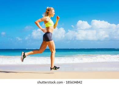 Athletic Woman Running on the Beach. Female runner jogging during outdoor workout.