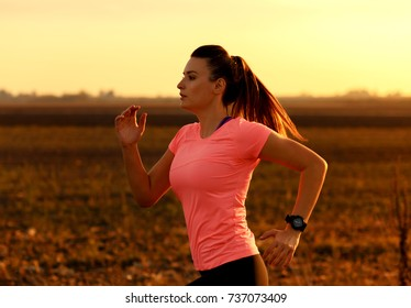 Athletic woman running on rural road during sunset.