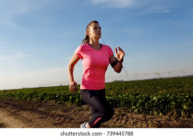 Athletic woman running on rural road.