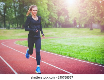 Athletic woman running on track, healthy fitness lifestyle