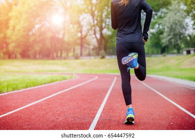 Athletic woman running on track back view, healthy fitness lifestyle