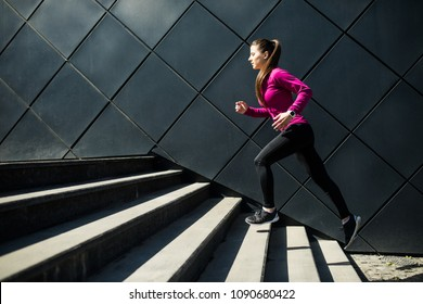 Athletic woman running up stairs during cardio