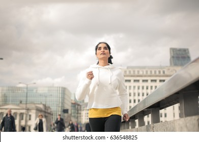 Athletic woman running in the street