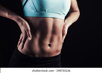 Athletic woman showing strong body and abs