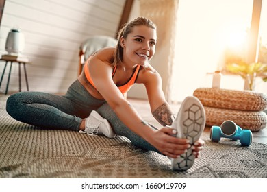 Athletic woman in sportswear doing fitness stretching exercises at home in the living room. Sport and recreation concept. - Shutterstock ID 1660419709