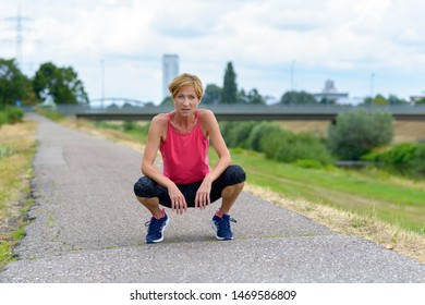 Athletic woman squatting for a rest after a workout jogging along a rural road on a cloudy summer day