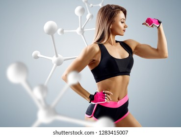 Athletic woman standing near white molecule chain. Good metabolism concept.