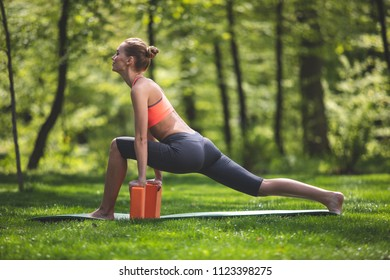 Athletic woman is staying in deep lunge on yoga map. She is training with blocks on green lawn. Sport in nature solitude concept