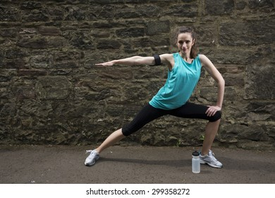 Athletic woman stretching before or after training. Action and healthy lifestyle concept.