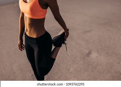Athletic woman stretching quadriceps during the warm-up on the beach. Athlete in sports wear exercising before her run. Cropped shot.