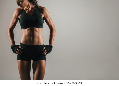 Athletic woman with strong abdominal muscles posing with her hands on her hips in shadowed light to emphasise her physique, with copy space