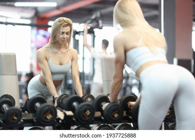 Athletic woman takes dumbbells in gym closeup