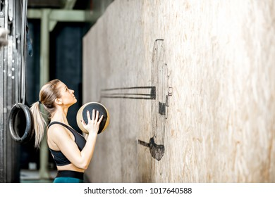 Athletic woman throwing a wall ball in the gym