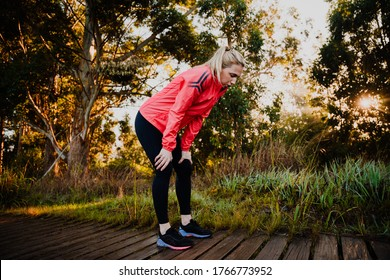 Athletic woman tired from run in the park, bent over breathing heavily