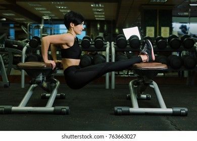 Athletic woman training arms muscles doing triceps dips in fitness club or gym