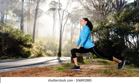 Athletic woman warming up before her morning workout in the forest mountain road. Runner training outdoors, healthy lifestyle concept.