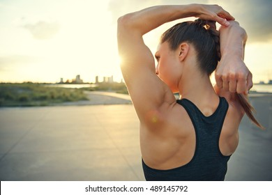 Athletic woman warming up before a workout standing facing the early morning rising sun on a rural road doing stretching exercises, close up with copy space