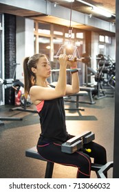 Athletic woman working out on a lat pulldown machine. Lat pull down machine woman workout at gym.