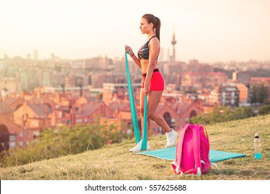 athletic woman working out with resistance bands in the park, against a blurred background of a city