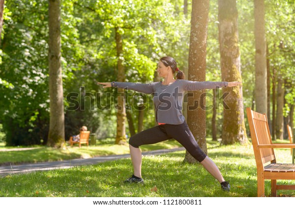 Athletic woman working out in a spring park amongst shady green trees doing stretching exercises
