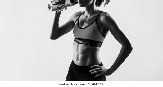 Athletic women. Beautiful young sporty girl. Athlete in motion. black and white photo. Female abdomen. one caucasian woman runner jogger drinking in silhouette studio isolated on white background