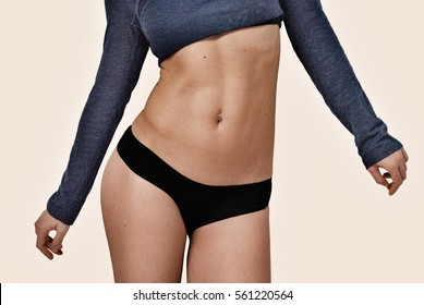 Athletic women belly on beige background. Front view. Close-up
