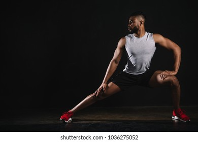 athletic young african american man in sportswear exercising and looking away on black