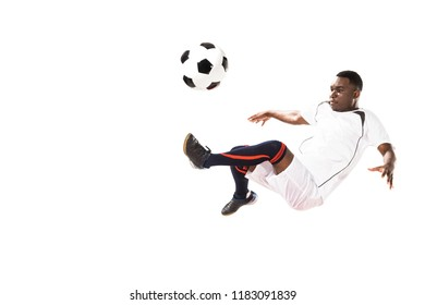 athletic young african american soccer player kicking ball in jump isolated on white