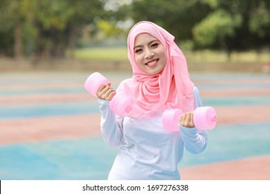 Athletic young asian muslim woman in sportswear standing and lifting dumbbells outdoor for morning exercise. Active girl work out on biceps exercise with green tree background. Sport concept