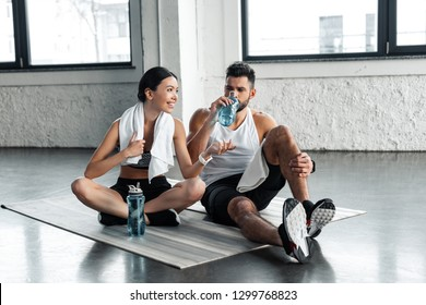 athletic young couple drinking water and resting on yoga mats after workout in gym