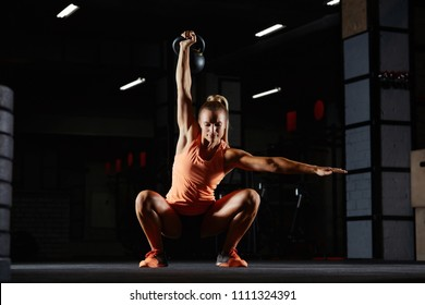 Athletic young crossfit woman performing overhead kettlebell squats at the gym, balance weights, weightlifting. Attractive female doing kettle bell exercise in the gym. Fitness woman working out.