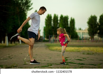 Athletic young father and little daughter do exercises in stadium. Healthy lifestyle