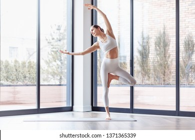Athletic young female yoga instructor doing vrikshasana standing near the large windows of the gym. Concepts of flatfoot correction and poor posture