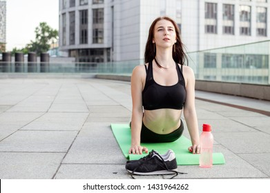 athletic young girl doing yoga in the morning on the street, she does stretching against the background of the city, fitness woman trains on the mat