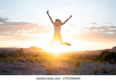 Athletic young girl jumping freely at mountain top against sunset in Murcia, Spain. Doing exercise work out, training. Attractive fit healthy woman in grass field smiling in the air. Fitness