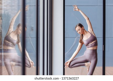 Athletic young girl yoga instructor doing vrikshasana standing near the large windows of the gym. Concepts of flatfoot correction and poor posture