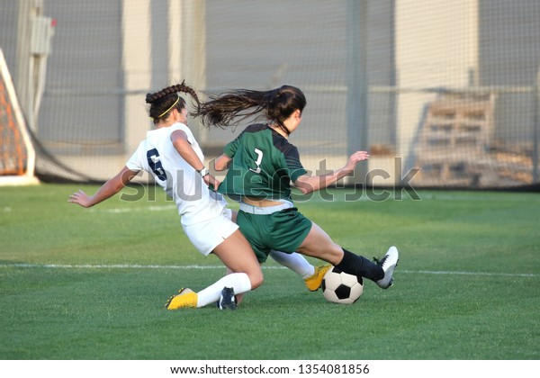 Athletic young ladies playing a varsity high school soccer game on a grass field