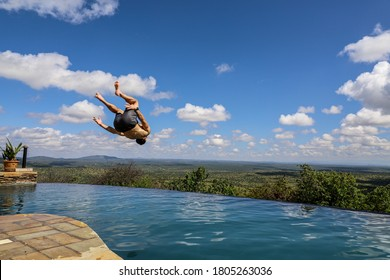Athletic young man doing backflip into infinity pool against beautiful blue sky with clouds background during summertime in Africa
