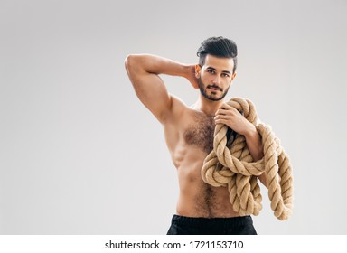 Athletic young man doing crossfit exercises with a rope on grey background.