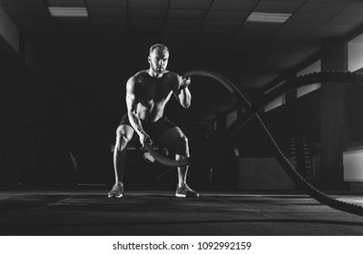 e83cea926eb3a Athletic young man doing exercise in the fitness gym. Sports concept.