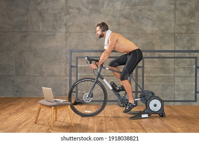 Athletic young man having stationary bike workout at home